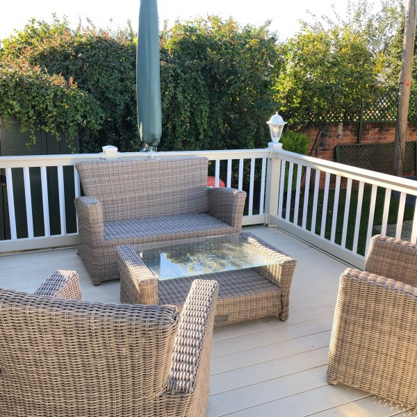 Static caravan with large outdoor deck seating area.